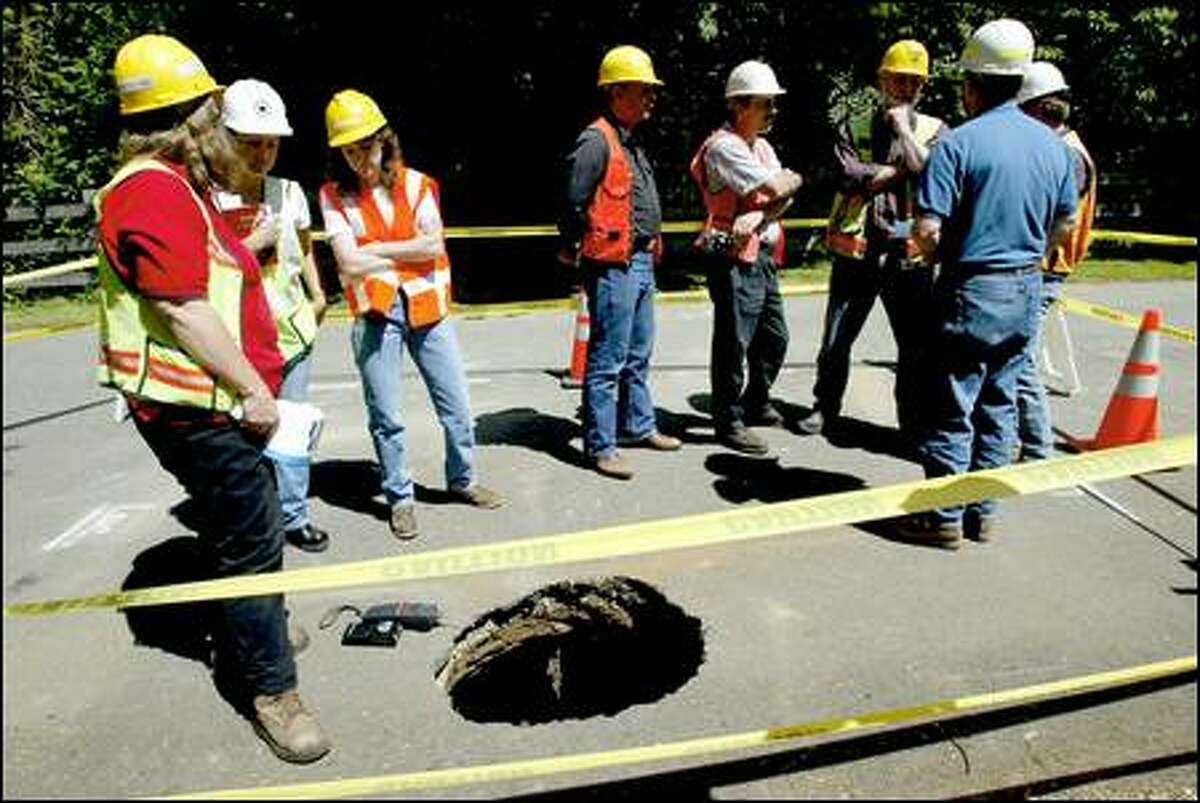King County transportation employees inspect a hole on 164th Avenue Northeast in Woodinville.