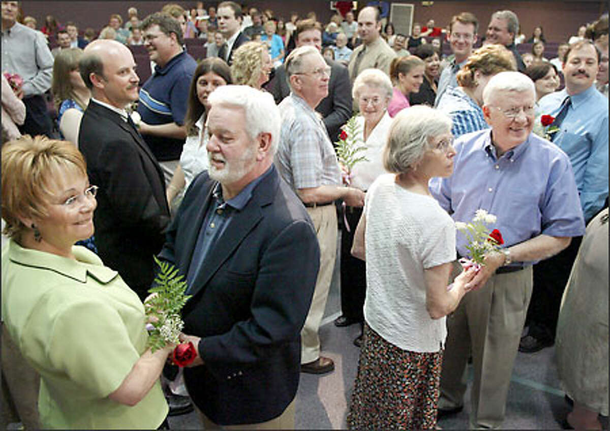 Marsha and Ed Waage of Snohomish and Donna and Sam Friend, front right, of Bothell renew their wedding vows with approximately 80 other couples yesterday at the First Baptist Church in Bothell.