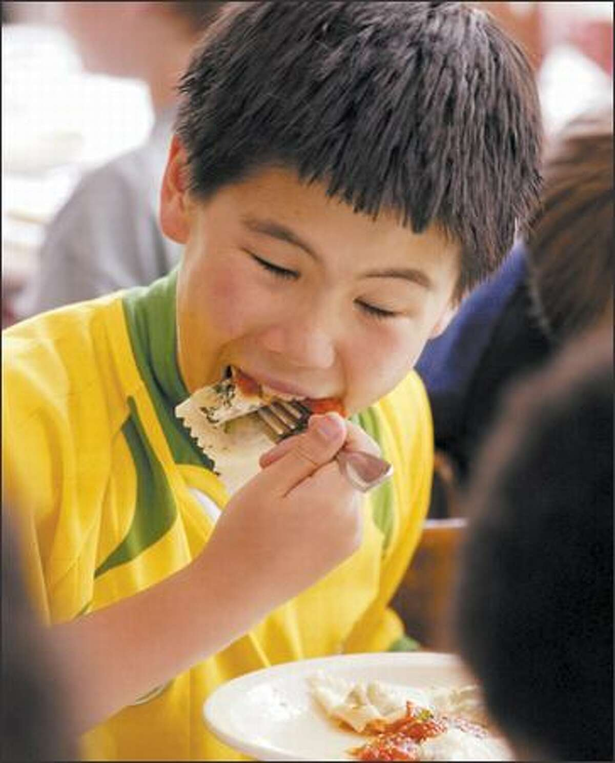 Student Jimmy Bromley takes a big bite of ravioli stuffed with herbs grown in Montlake Elementary's school garden.