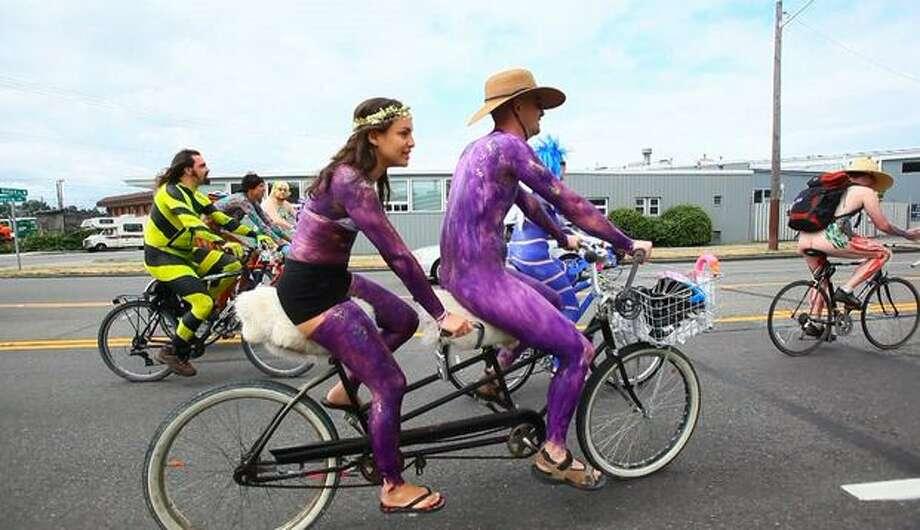 Monica Guzman and Jacob Sayles ride on a tandem bicycle through Ballard. Photo: Joshua Trujillo, Seattlepi.com / seattlepi.com