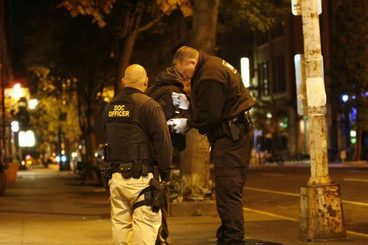 Christopher Salindron, left, and Kris Rongen with the state Department of Corrections stop a man in the 2300 block of First Avenue in Seattle last fall. The man was found with heroin and arrested.