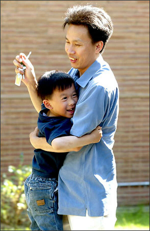Leon is happy to see his father, Kele Hu, who's come to pick him up from Head Start. Photo: Mike Urban, Seattle Post-Intelligencer / Seattle Post-Intelligencer