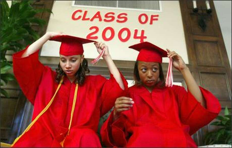 Graduates Lesette Kinz, left, and Brianna McMillon adjust their caps and tassles before the YMCA's Seattle Rotary Education Center graduation last week. Photo: Dan DeLong, Seattle Post-Intelligencer / Seattle Post-Intelligencer