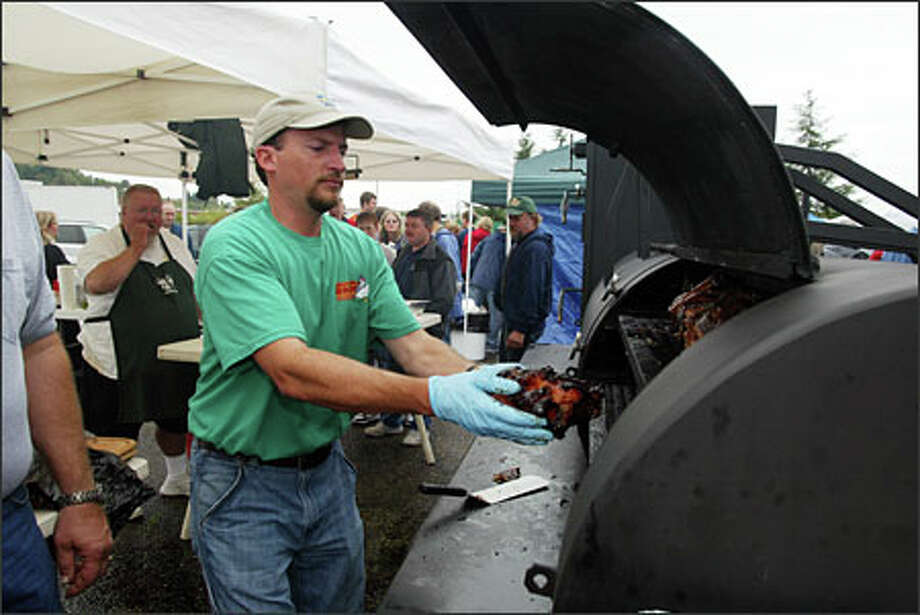 The team of Ray Lampe, left, and Chris Lilly prepare their entry at last year's Low & Slow State BBQ Championship. Photo: Gilbert W. Arias, Seattle Post-Intelligencer / Seattle Post-Intelligencer