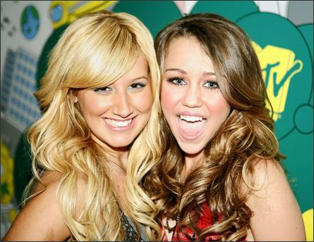 What makes these girls more than cute? Good dentists help, and hairdressers standing by. Ashley Tisdale, left, and Miley Cyrus pose backstage during MTV's