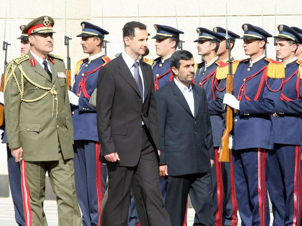 Iranian President Mahmoud Ahmadinejad, right, and Syrian President Bashar al-Assad review an honor guard at Al-Shaab presidential palace on Feb. 25 in Damascus, Syria. On the eve of Ahmadinejad's visit, the Obama administration said it was pressing Syria to move away from ally Iran and stop arming Hezbollah. Syria had announced earlier that Ahmadinejad will visit Damascus to hold talks with Assad, whose government says it wants to help Iran and the West engage in a