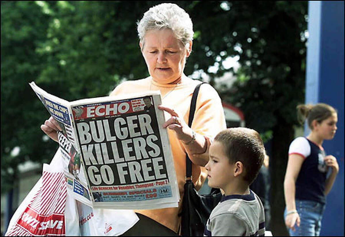 Barbara McHugh and her grandson Alex read a newspaper article in Bootle, England, about the release of little James Bulger's killers.