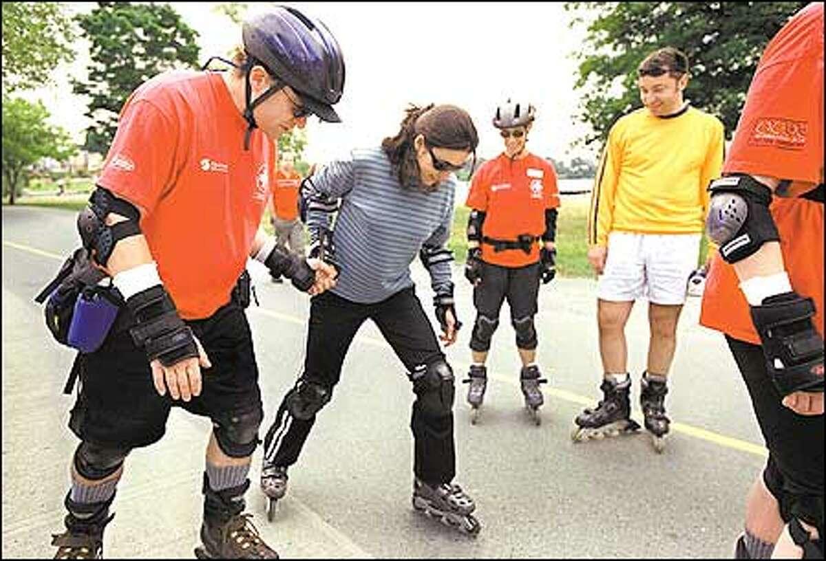 Eirik Nalder, left, a National Skate Patrol volunteer, lends Dolores Diaz a hand with her technique.