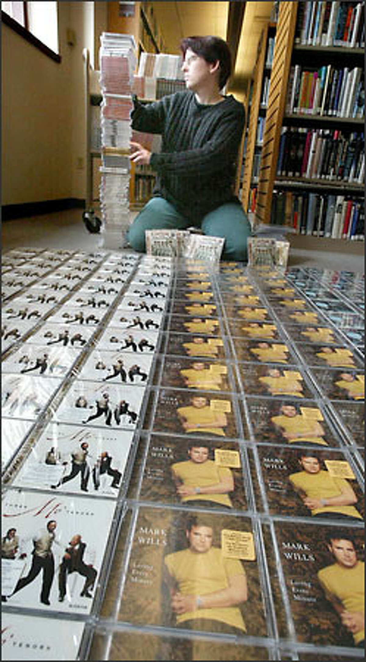 Lara Weigand, librarian for Tacoma Public Library, checks out some of the CDs the library received as part of the music industry settlement. The large number of little-known CDs has disappointed Weigand.