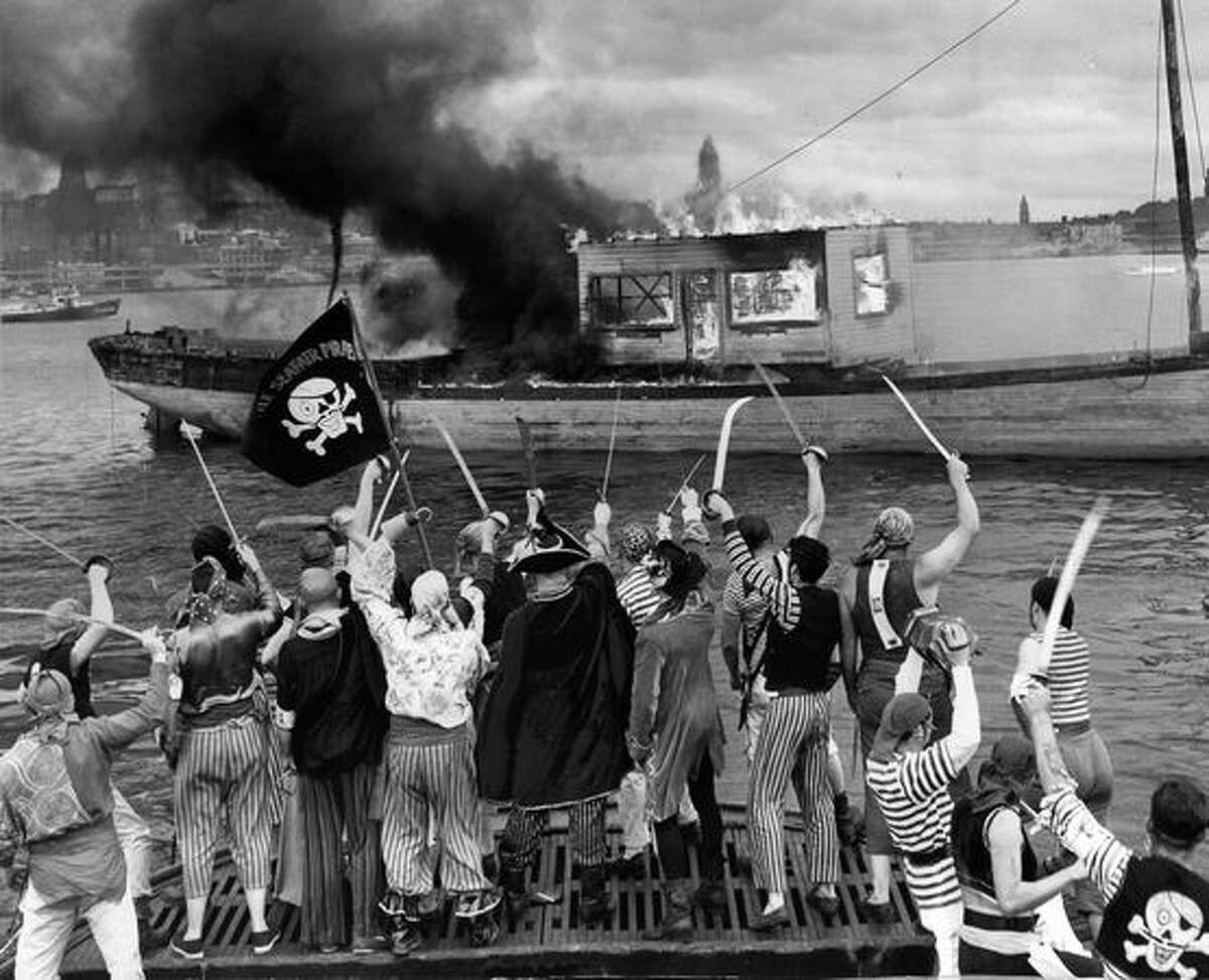 Seafair Pirates of 1955 stand on the tugboat Tyee as they watch an 80-year-old sailing ship burn in Elliott Bay. In the early years of Seafair, the pirates would burn the flagship of King Neptune.