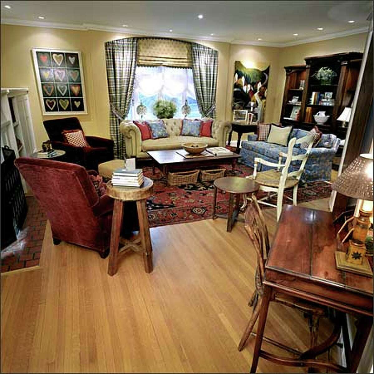 To accommodate more people in this combination family room and entertaining area, chairs and couches have been added and arranged in conversational groupings. Along the back wall, a tall bookcase holds books, photo albums and memorabilia and functions as a small library.