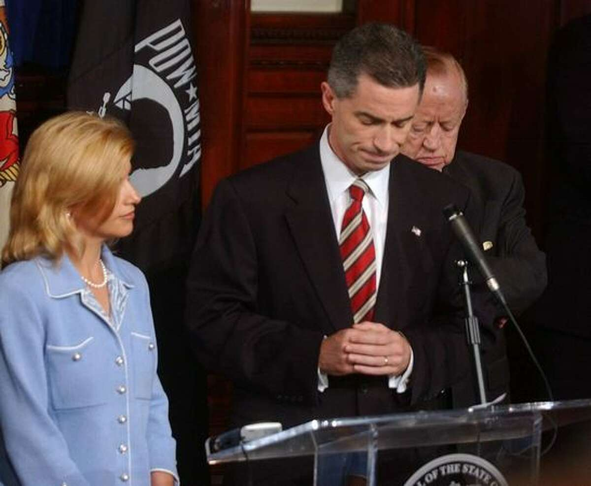 In this Aug. 12, 2004 file photo, Dina Matos McGreevey, left, stands next to her husband Gov. James E. McGreevey as he announces he will resign in November during a news conference at the Statehouse in Trenton, N.J. where also admitted he had an extramarital affair with another man.