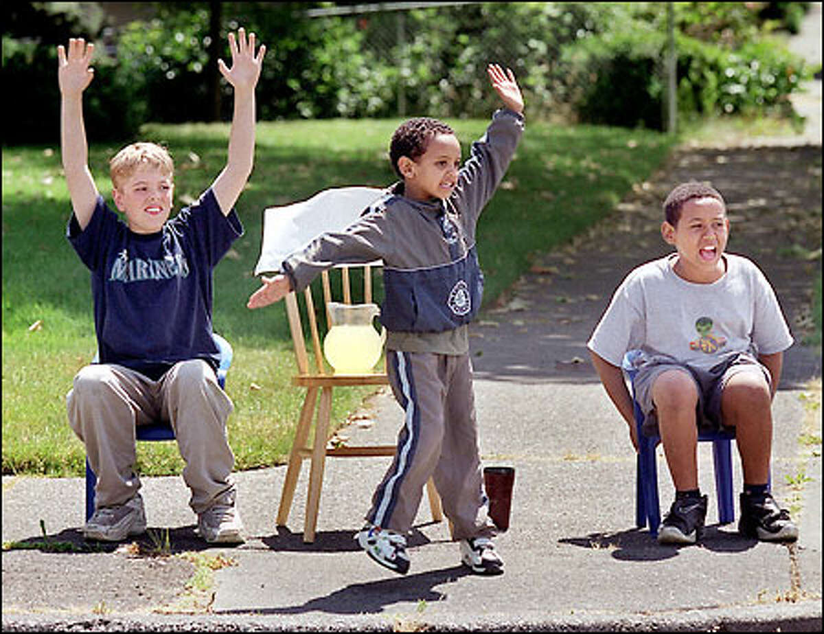 Andy Nelson, 11, left; Aaron Mengstav, 5, center; and Abraha Mengstav, 11, flag cars while they sell lemonade at Southwest Charlestown Street and 48th Avenue Southwest.