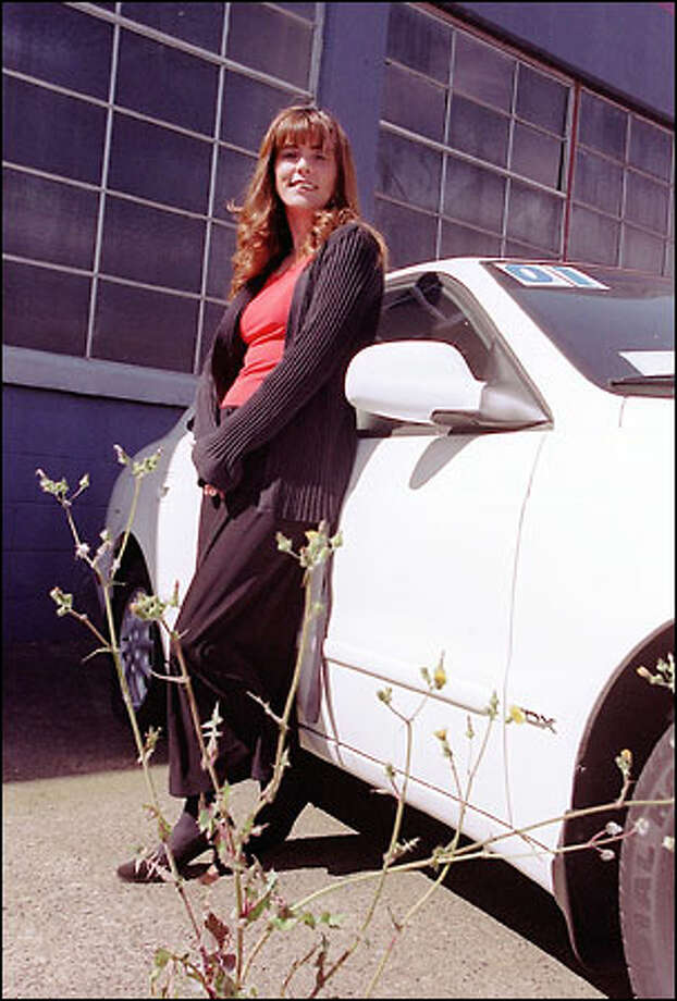 Dana McGiboney, office manager for Three Sisters Nelson Chevrolet in Ballard, stands with a leftover Daewoo and the symbolic weeds that have grown up around it. Photo: Phil H. Webber, Seattle Post-Intelligencer / Seattle Post-Intelligencer