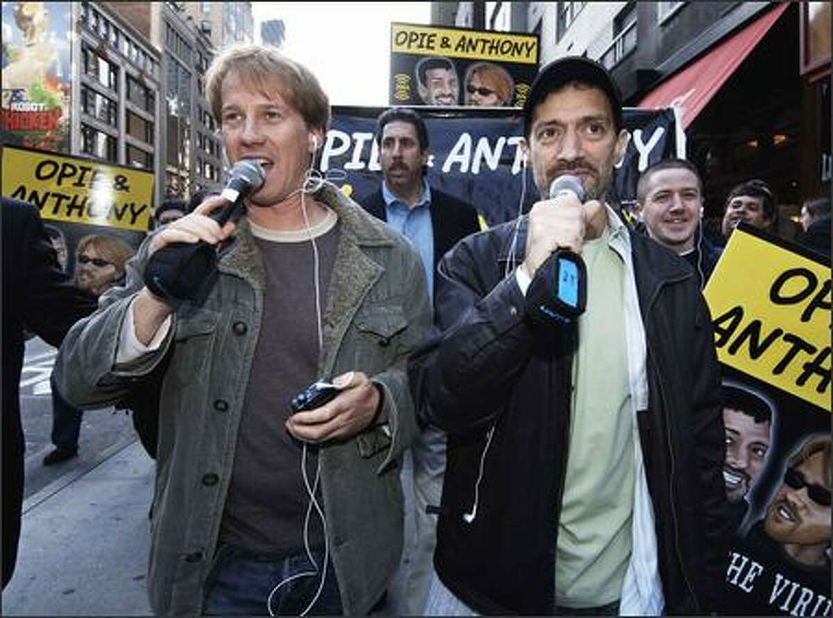 """Shock jocks Greg """"Opie"""" Hughes, left, and Anthony Cumia greet New York fans after finishing their first morning show for XM last April. Since then, they've become radio ratings kings, starring on satellite and terrestrial formats. Four years ago, they were yanked off the air for a """"sex in St. Patrick's"""" stunt. Don't ask."""