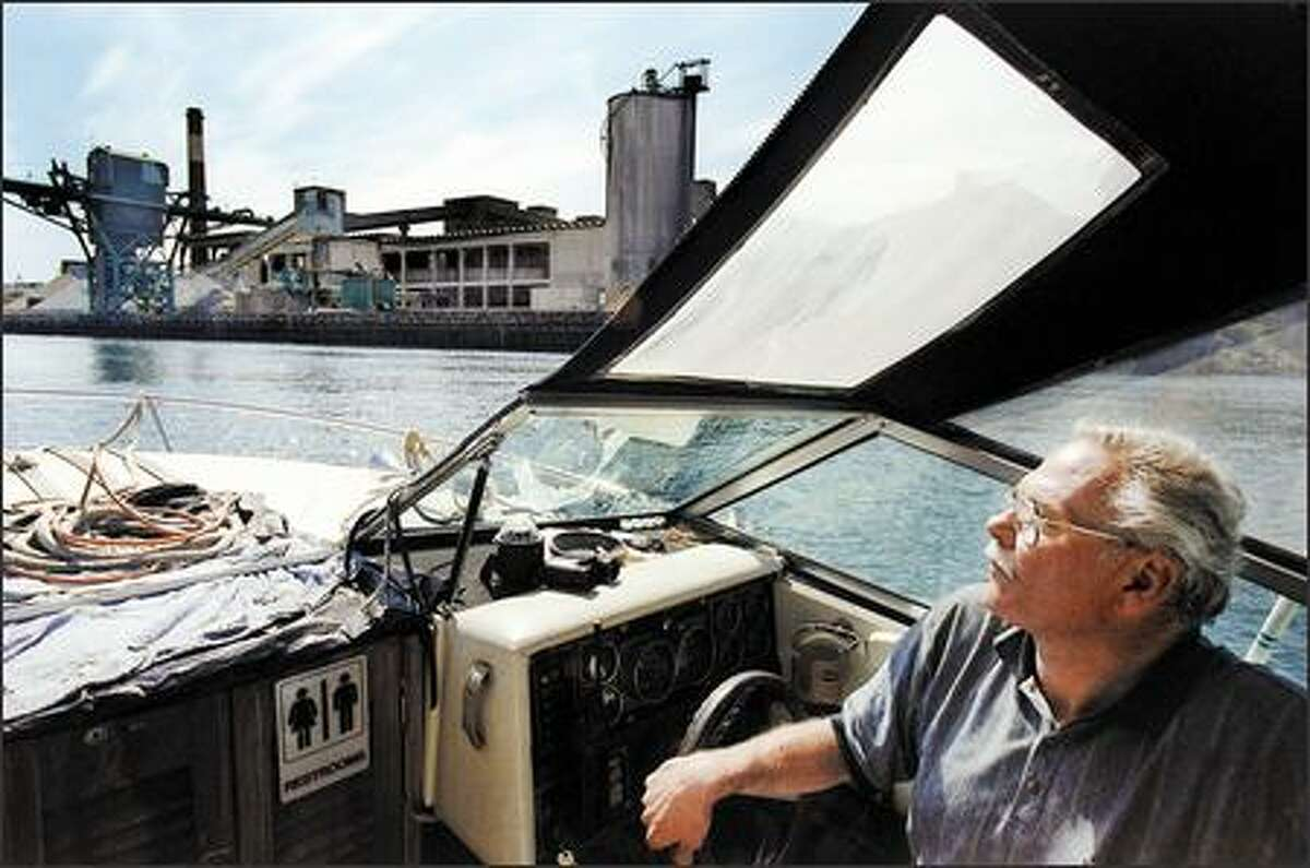 John Beal, steering his boat upstream on the Duwamish River in 2002, spearheaded efforts to restore habitat along the river. (P-I file)