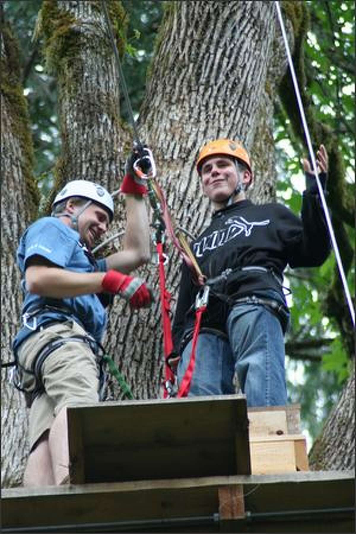 High in a treetop perch at zipline No. 4, Fraser McGee gets his harness attached by guide Cole Carnes.
