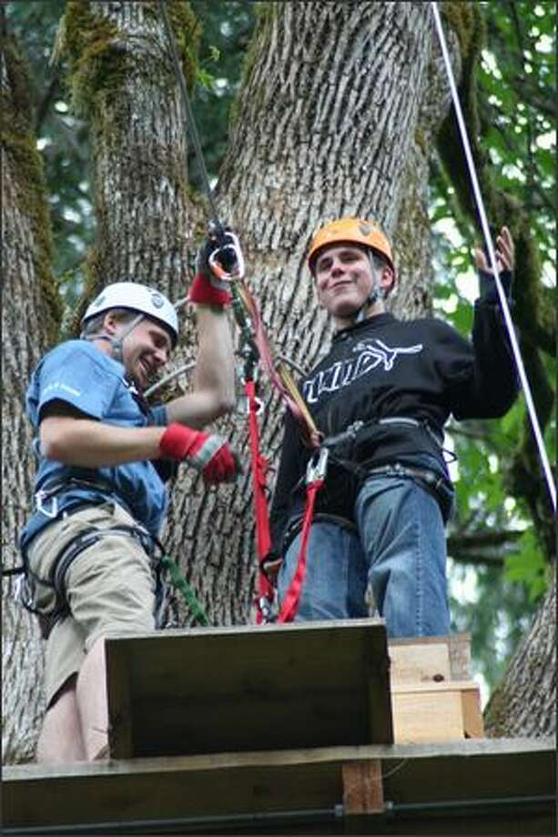 High in a treetop perch at zipline No. 4, Fraser McGee gets his harness attached by guide Cole Carnes. Photo: Anne Mullens, Special To The Seattle P-I / Special to the Seattle P-I