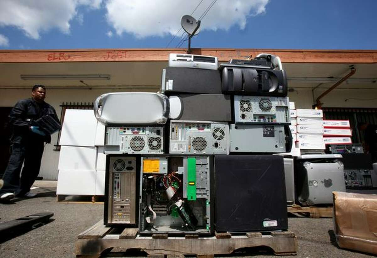 Seattle Police Det. Will Cravens helps stack computers in front of a business on Rainier Avenue South after police broke up what they say is part of a major computer theft ring.