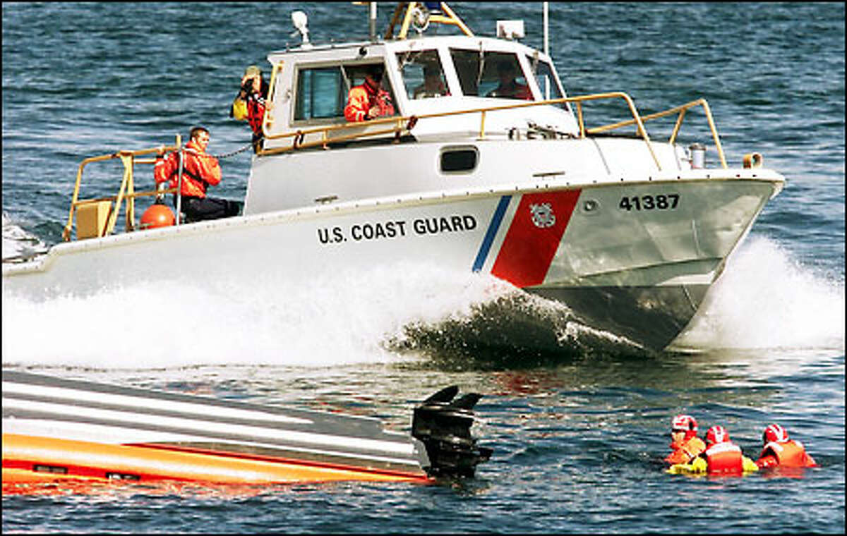 A 41-foot cruiser passes by as three members of the Coast Guard try to swim to the hull of their capsized 23-foot runabout during a training drill.