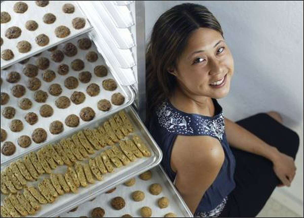 Mei-I Funtanilla poses with some of her recently baked miniature cookies, including milk chocolate chunk (top two racks), white chocolate pistachio biscotti (middle) and chocolate almond and vanilla brown butter (bottom), at her home bakery.