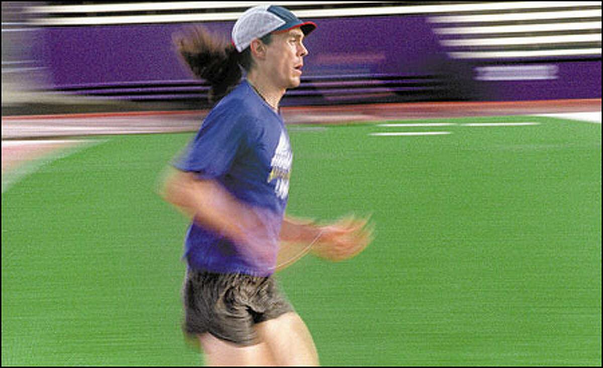 Slow shutter speed shows long-distance runner Scott Jurek working out in Husky Stadium.