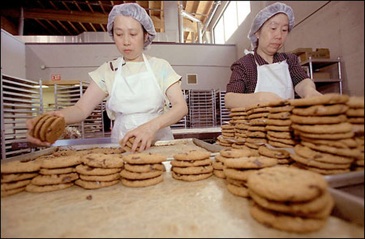 Fong Lau and Wan Li at work at Cougar Mountain Baking Co. on Sixth Avenue South in Seattle. The company sells between $1 million and $2 million worth of cookies a year.