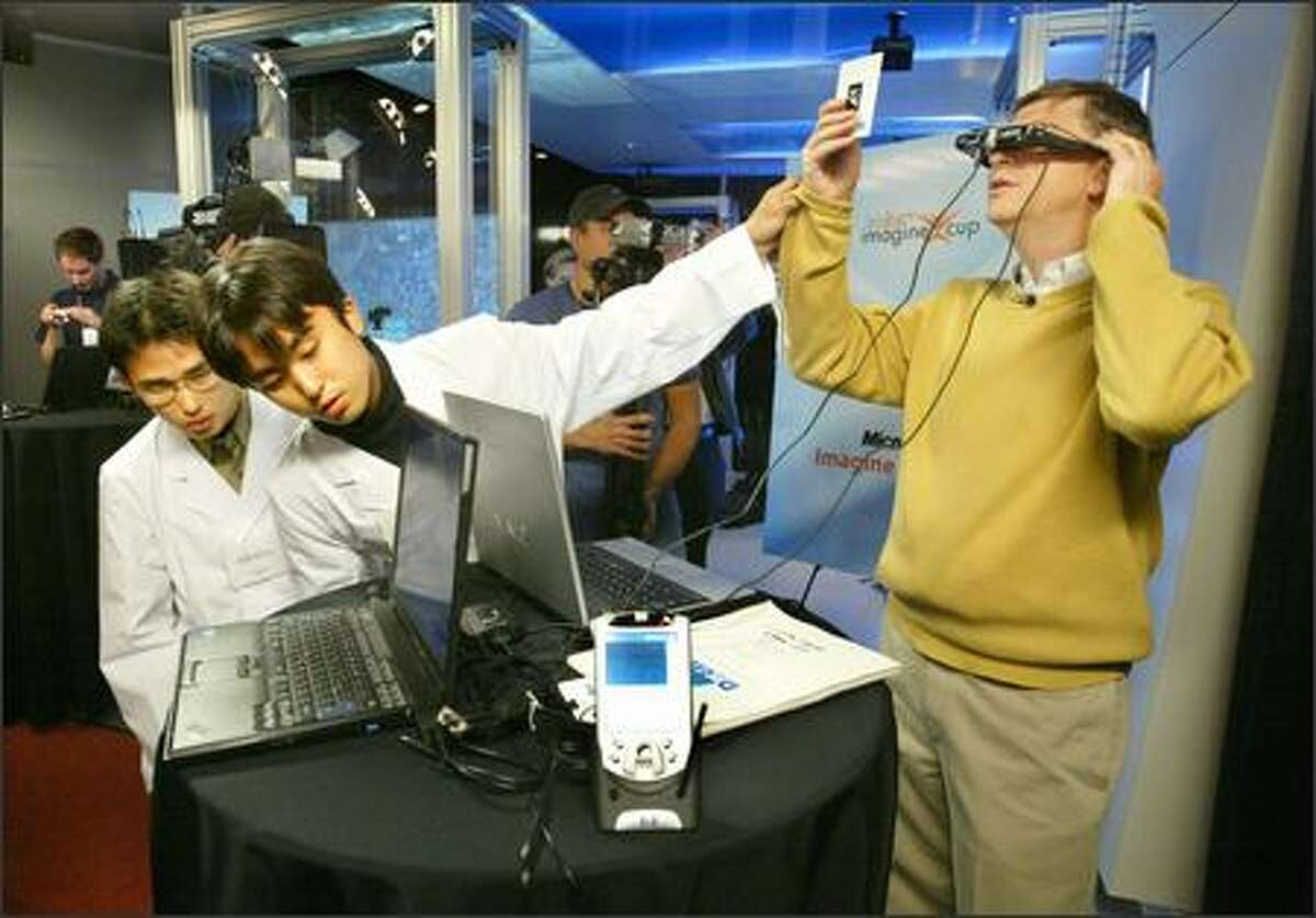 Yuichi Shiwaku, left, and Kotaro Nakayama of Team Japan show Microsoft Chairman Bill Gates how to use a 3-D viewer designed to help in patient treatment during a demonstration by Imagine Cup finalists at Microsoft's campus in Redmond on Wednesday.