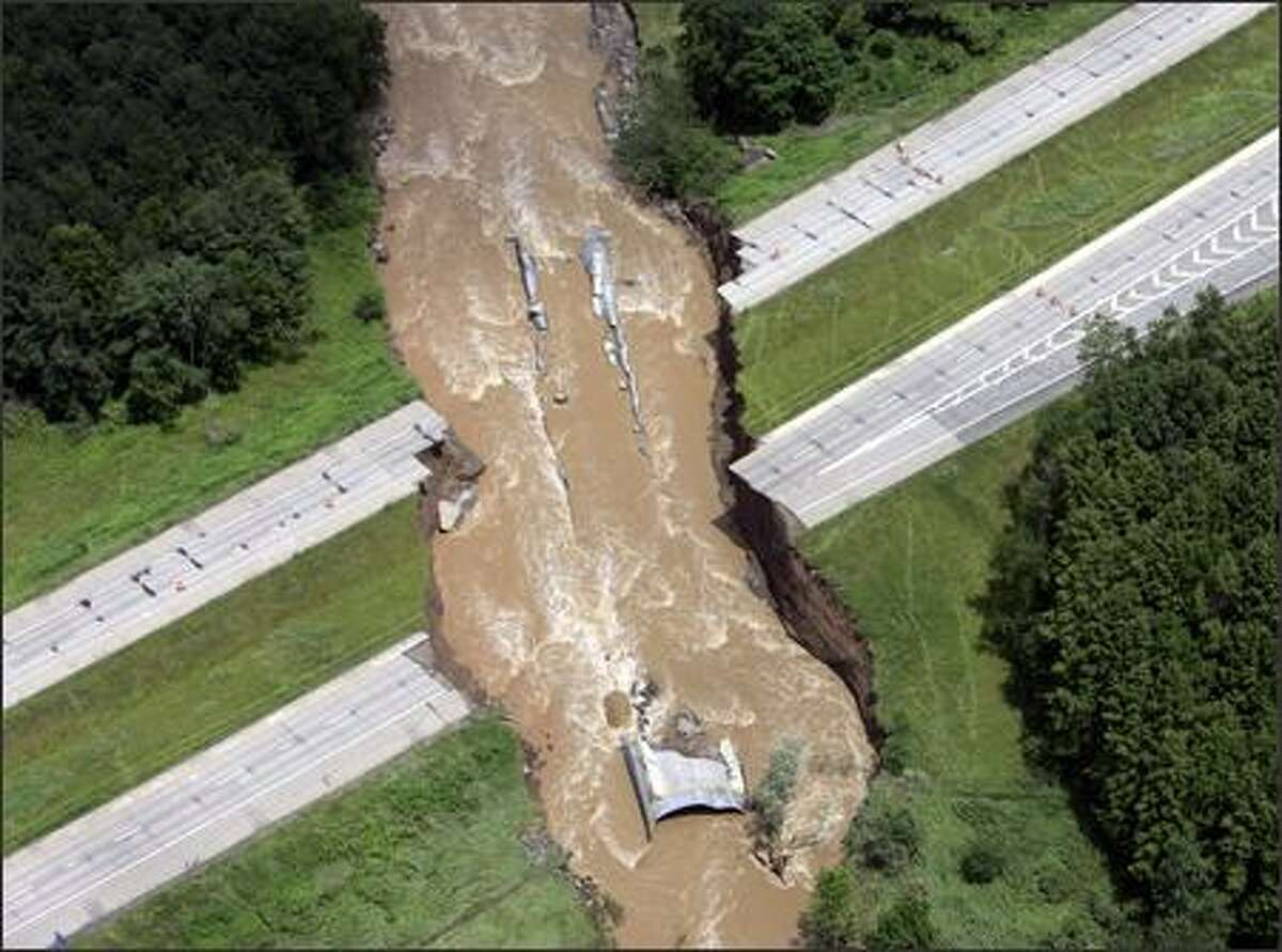 Flooding from Carrs Creek cuts through a section of Interstate 88 on Wednesday in Sidney, N.Y. Two truckers died after driving their trucks into the chasm. Record-breaking flooding has killed at least 12 people in the Northeast.