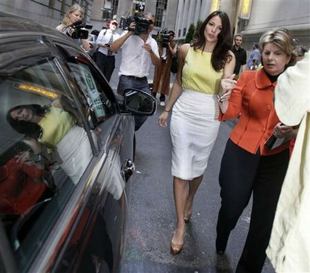 Debrahlee Lorenzana, center, who says she was fired from her banking job after complaining that male colleagues called her curvaceous figure distracting, and her attorney Gloria Allred, right, walk to a waiting car after a curbside news conference in New York's Financial District Monday. (AP Photo/Richard Drew)