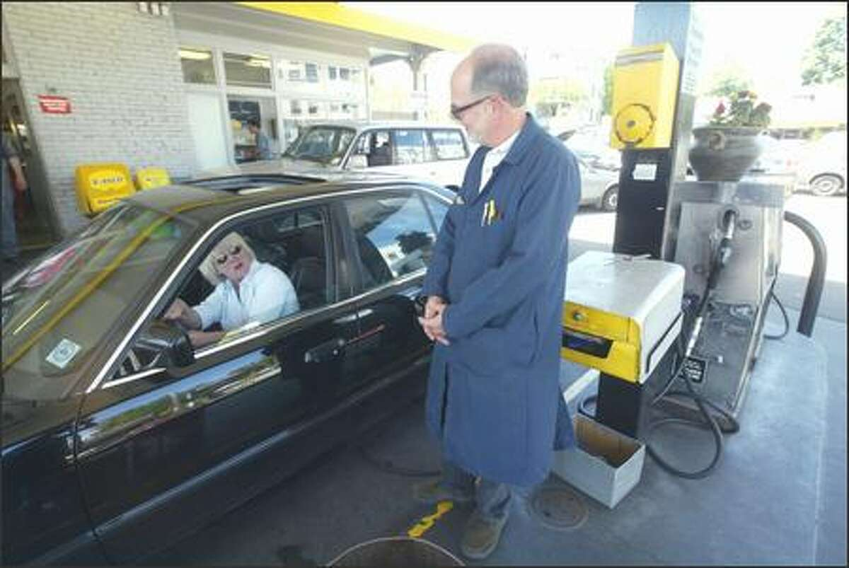 Michael Burke, owner of Hilltop Service Station and repair shop in Seattle, chats with customer Rebecca Larson, who has been going to the full-service gas station for 20 years. Full service is the rule at Hilltop, where customers aren't allowed to pump their own gas.