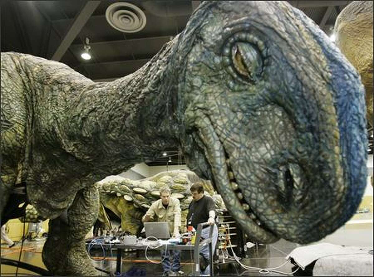Chief engineer Trevor Tighe, left, and David Fulcher, a hydraulic technician, make technical adjustments. Truck batteries, hydraulics and puppeteers are used to give the dinosaurs movement.