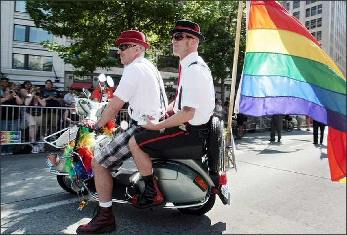 The Sqream Scooter Club rides in the Gay Pride Parade in Seattle on Sunday.