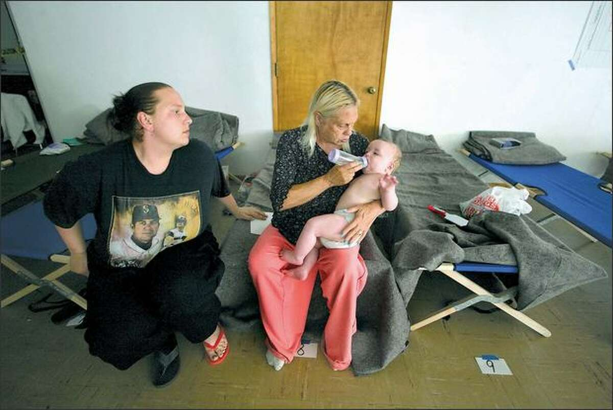 Liz Baggott watches as her mother-in-law, Jill Baggott, feeds 6-month-old Brandon Handran, their neighbors Joel Handran and Pamala Ward's son, at Lake Burien Presbyterian Church on Sunday. The three-alarm fire that killed three also injured six people and displaced about 40, with another 20 or so sheltering with friends or relatives.