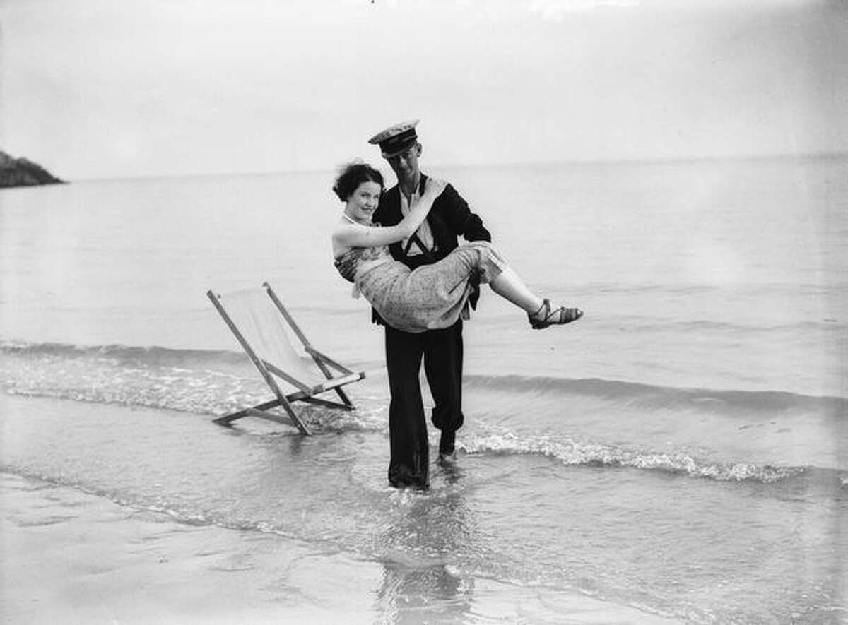 In this file photo from September 1937, a young lady falls asleep on the beach and has to be rescued from the advancing tide by a gallant deckchair attendant at Barry Island, South Wales.