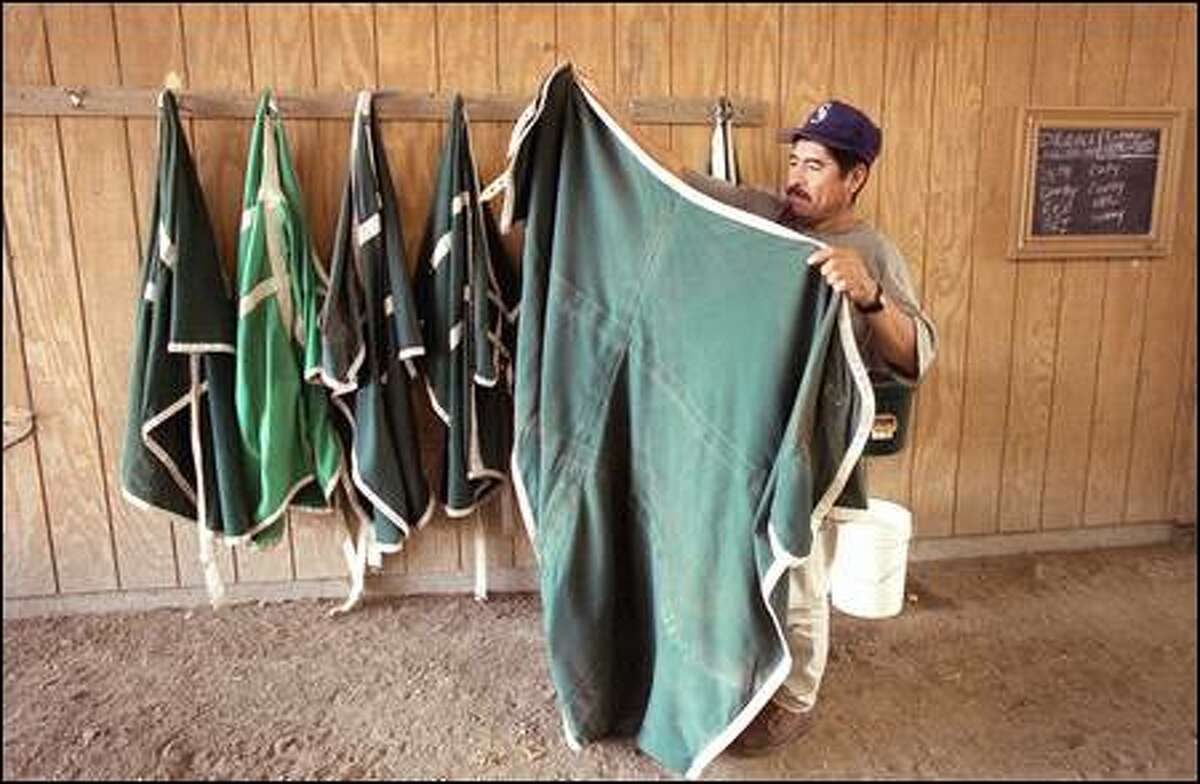 Jose Luis Faustino folds up a horse blanket after a day at work at Emerald Downs. Faustino is a groom at the track.