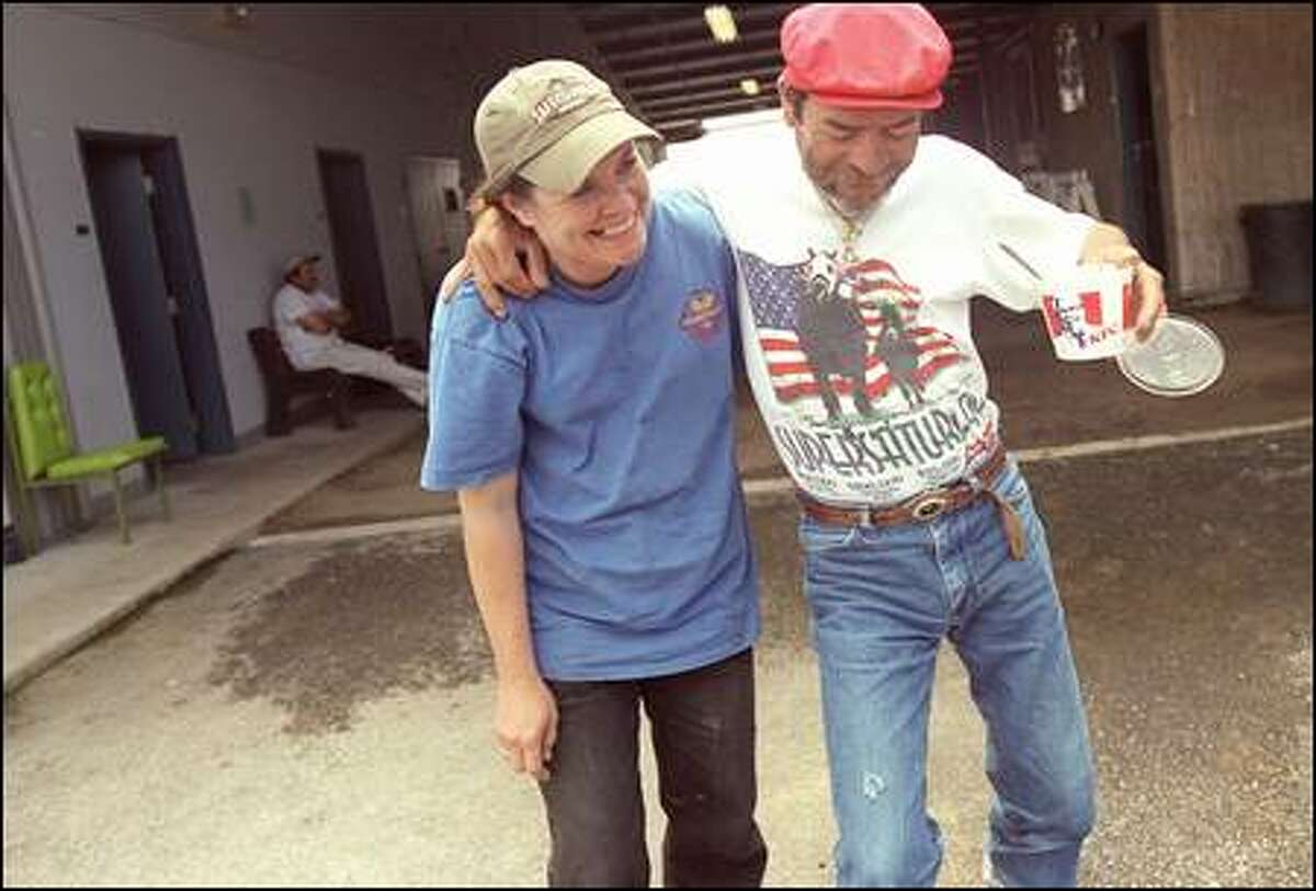 Joe Hernandez and Jeannie Willingham dance a jig during a long and hot day of work. Willingham is a groom and Hernandez is a jockey.
