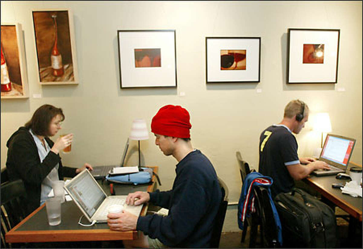 Victrola Coffee & Art customers, from left, Amy Coffman, Tim Matsui and Billy Perry take advantage of the free Wi-Fi at the Capitol Hill coffeeshop.