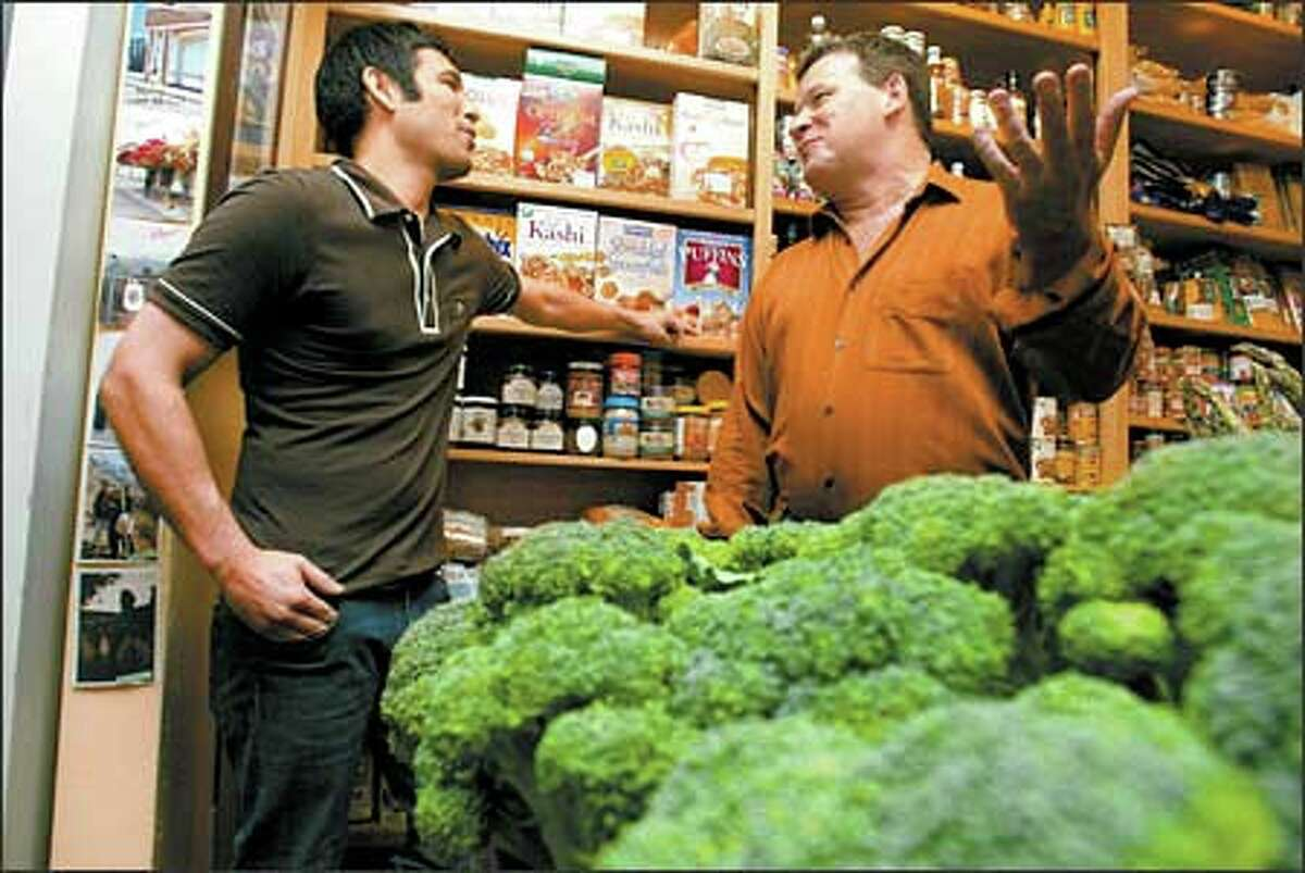 Former Sunset Hill Greenmarket owner John Mabbott, right, chats with new owner Chuck Genuardi. The first time they met, Genuardi says, he knew that their values clicked.