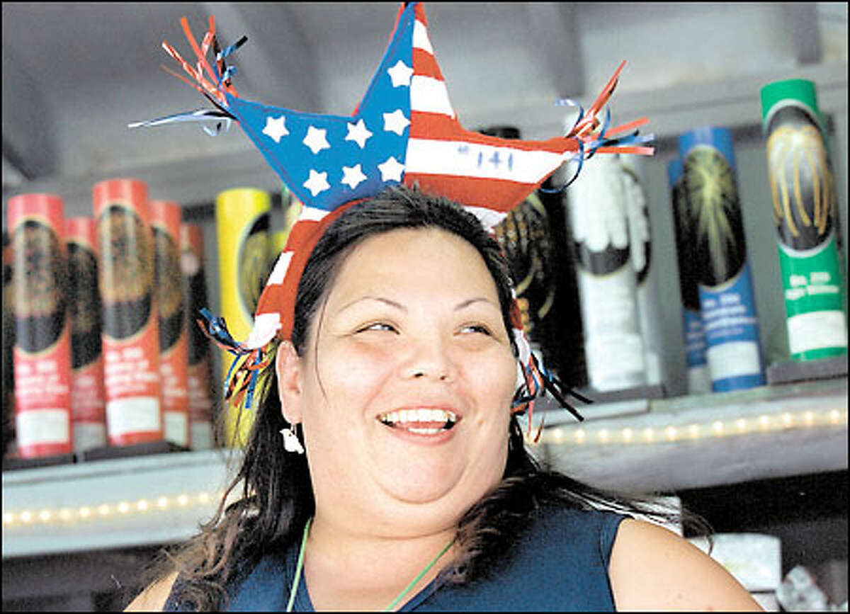 """Carmen Burke wears a hat to celebrate her birthday yesterday while selling fireworks on the Tulalip Indian Reservation. """"It has been really slow because of the rain but today it is going very good. We were all worried about whether people would find the new location at Boom City,"""" she said."""