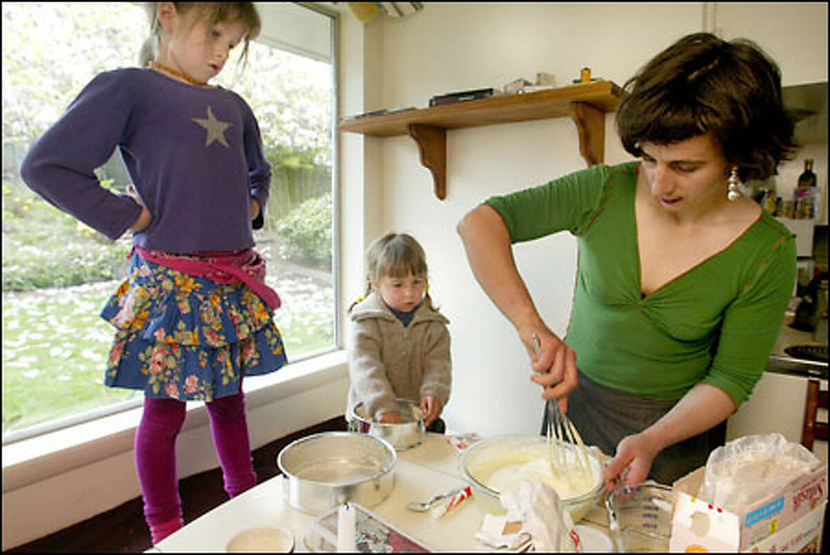 Sabine Maier makes a classic Black Forest cake for Luca's sixth birthday, while she supervises and younger sister Branca, 3, watches.
