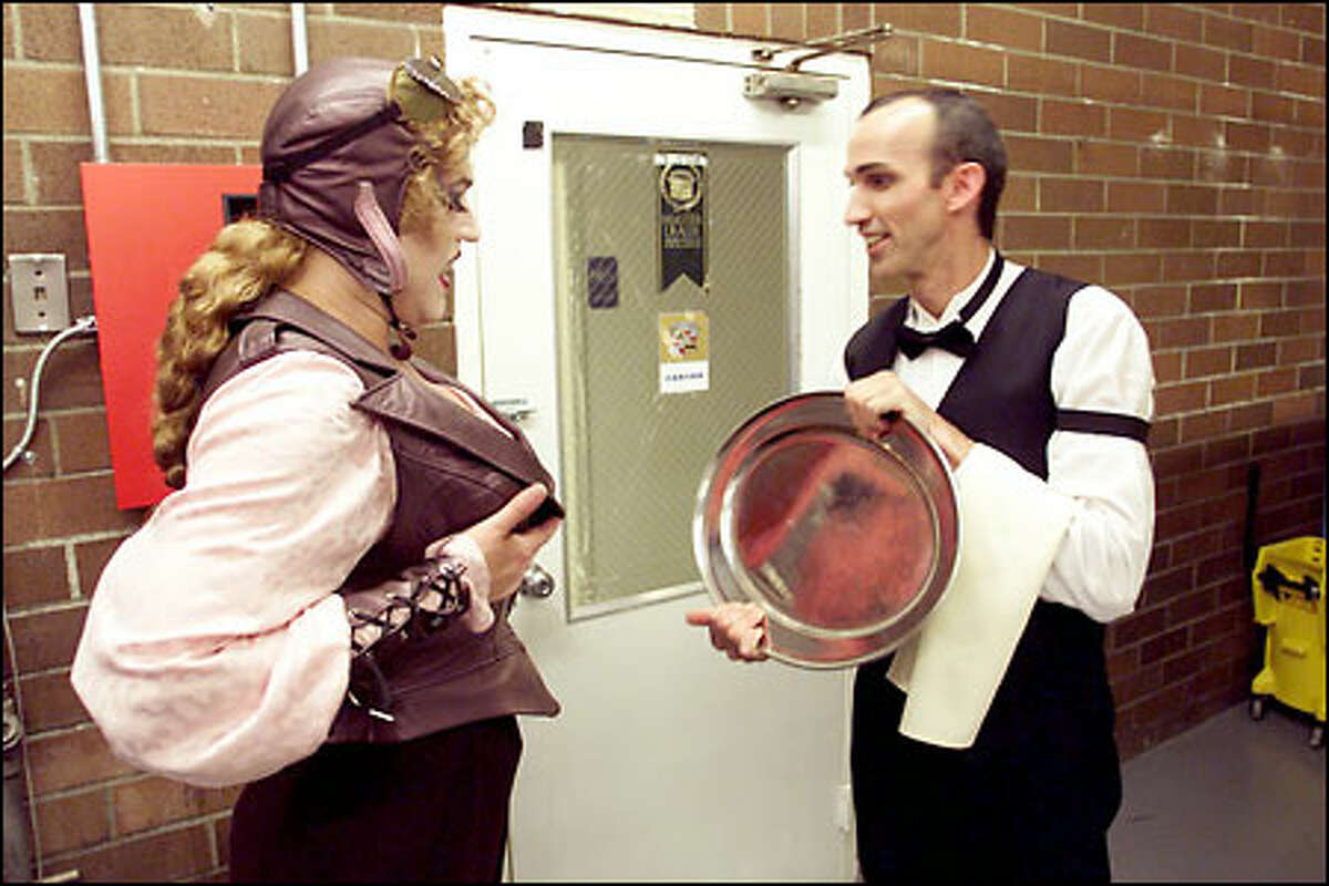 Teatro ZinZanni performer Kevin Kent adjusts his, ahem, costume in the reflection of Yogi Mohr's serving platter during the rush of a show.