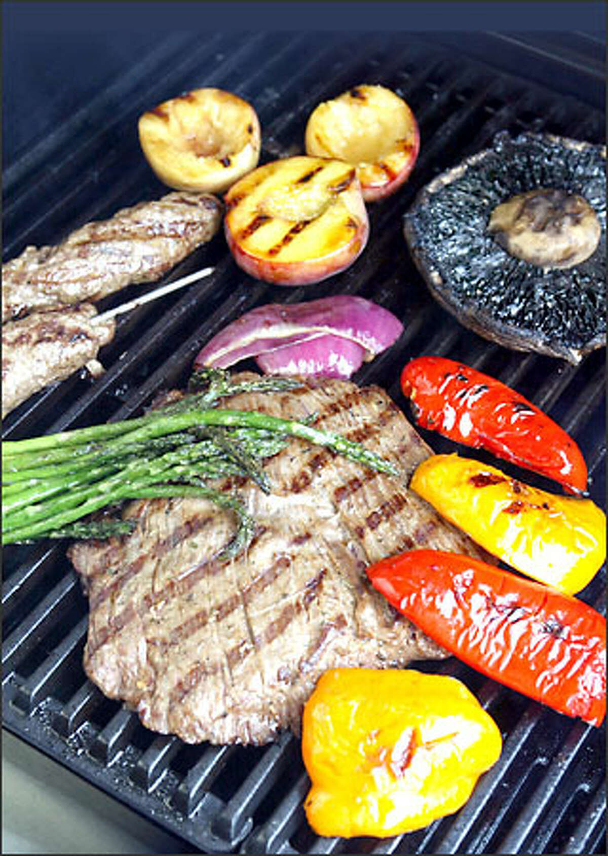 Grilling isn't just for burgers anymore. Here we have flank steak surrounded by peppers, asparagas, lamb kebobs, nectarines, onions and a portabello mushroom.
