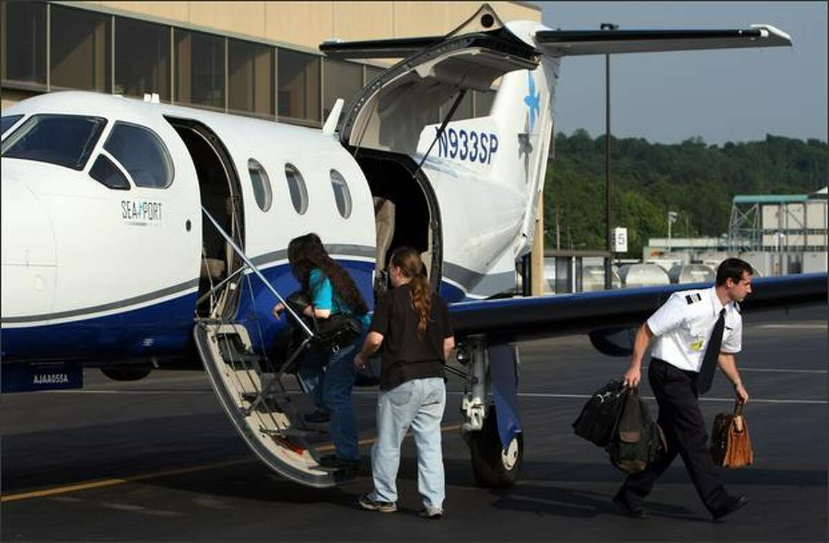 Passengers board a nine-seat SeaPort Airlines plane at Boeing Field on Tuesday. SeaPort started flying the Seattle to Portland route Monday.