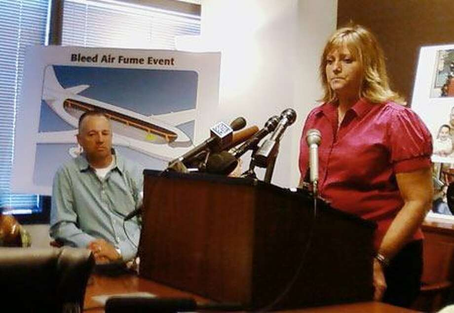 Former flight attendant Terry Williams speaks to reporters Wednesday as her husband, Gary, looks on. Williams, 40, claims she was poisoned by tainted air drawn into a plane on which she was working due to a design flaw present in most commercial airliners. Photo: Seattle Post-Intelligencer