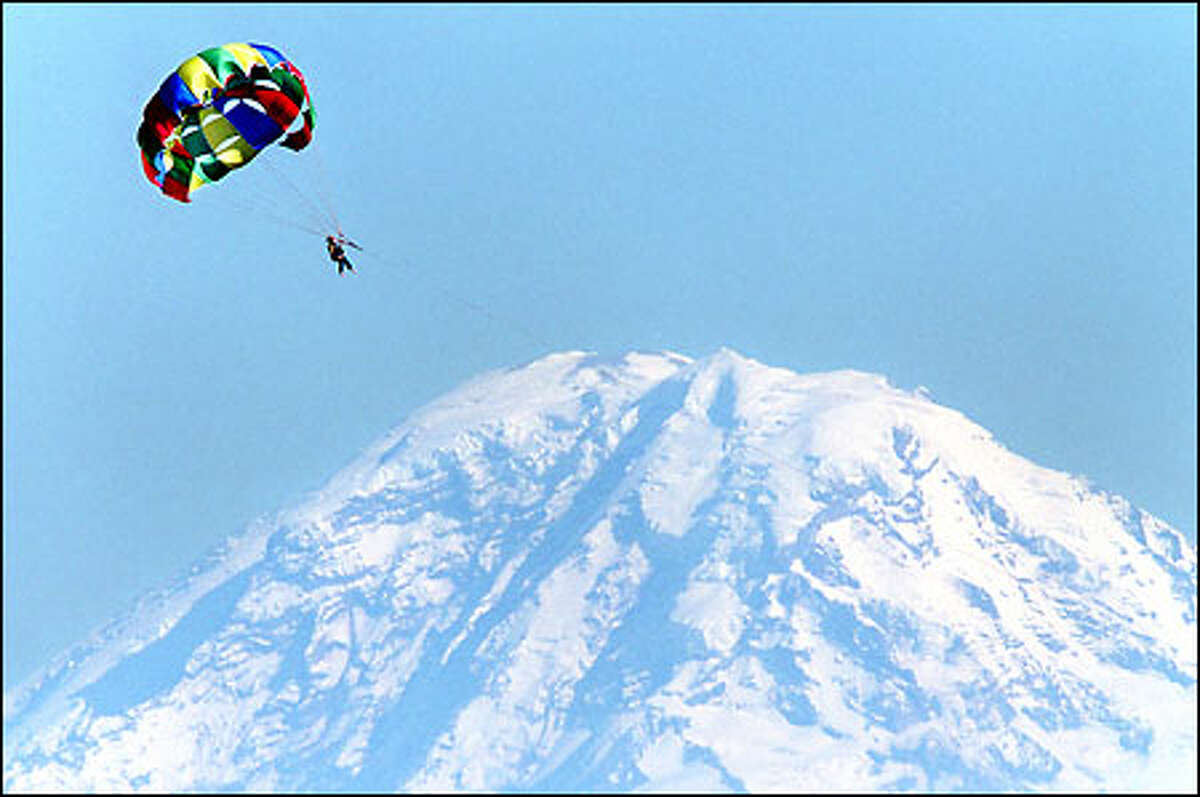 High above Elliott Bay, a parasailor seems to slip the bonds of Earth while going for a ride on a beautiful summer day. It appears the adventurer would land atop Mount Rainier, but that is just the camera tricking us -- a super-long lens was used to achieve the effect. Today should be a near-perfect day to enjoy the holiday -- or parasail over Mount Rainier.