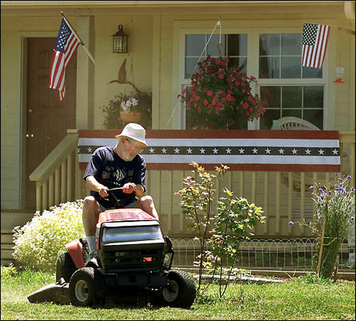 Rudy Onstaqd, who lives about a quarter of a mile from the site of the big fireworks show, cuts his lawn as he gets ready for friends and relatives who will join him.