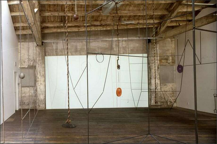 In Carolyn Healy and John Phillips' installation, interlocking metal rods become rectangles, triangles and the graceful fall of two diagonals, with cables, ropes, weights and pulleys. Steel shades dominate with a scattering of brighter shades. (EDUARDO CALDERON)