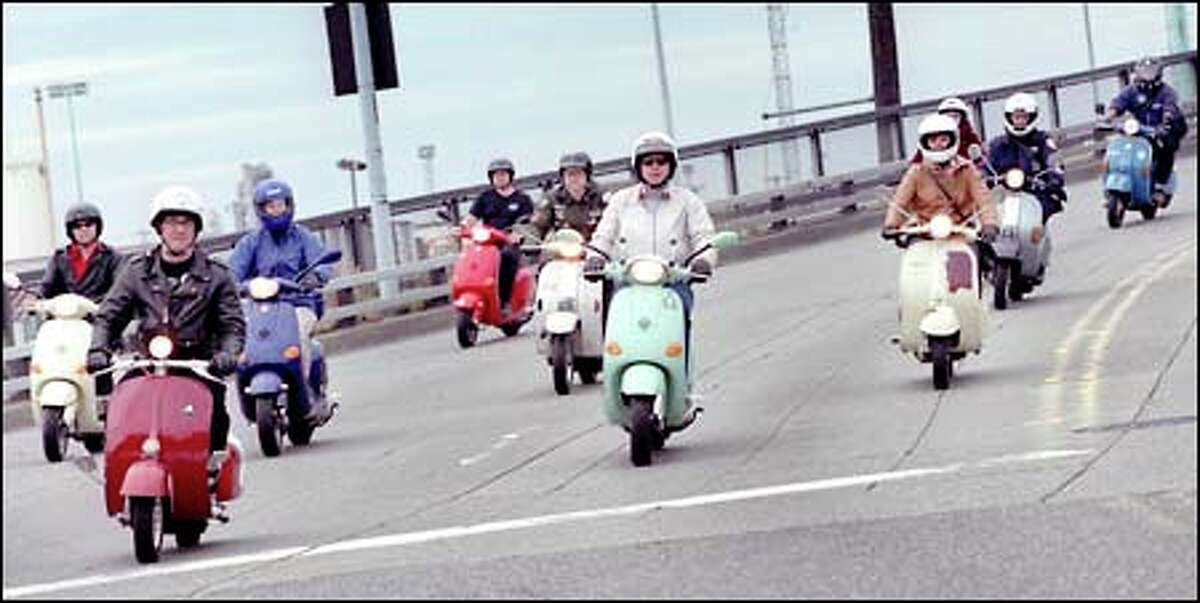 """Rolling across a Seattle overpass, a colorful collection of scooters hints at what's to come at local """"Scooter Insanity"""" gatherings in which owners can inspect new and vintage scooters and participate in group rides."""