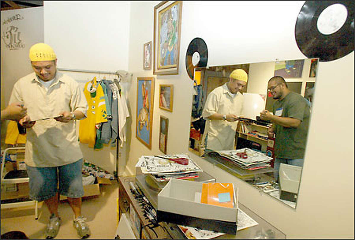 Curator George Quibuyan, left, discusses material with Darvin Vida (shown in mirror) while setting up the exhibit.